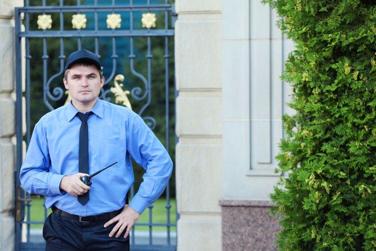 Sicherheitsmann bewacht Einfahrt zu teurem Haus.