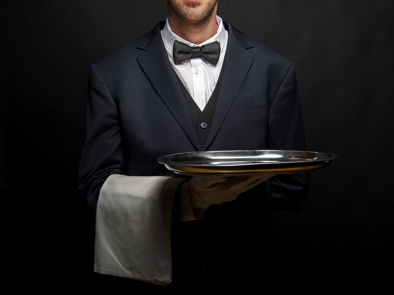 Servicedienstleister hält ein silbernes Tablett in der Hand und ein weißes Handtuch über dem Arm.