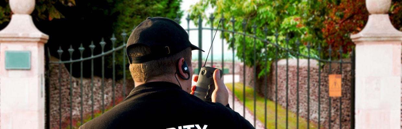 Sicherheitsmann steht vor einem Einfahrtstor und spricht in ein Walkie-Talkie - GSK Veranstaltungsservice